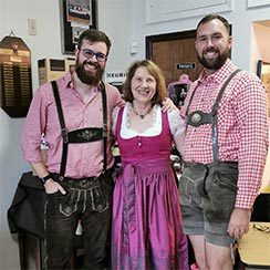 Three adults in traditional German costume including lederhosen