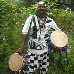 Drummer in black and white African dress carrying two drums standing outside