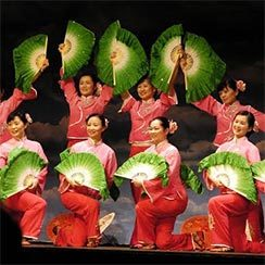 Ten dancers wearing red carrying large green folding fans