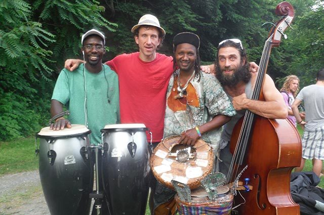 Four men standing outside with percussions and large stringed instrument