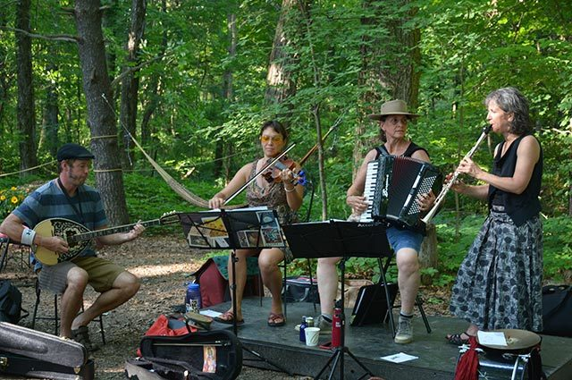 Folk band playing mandolin, violin, accordion and clarinet on stage in the woods