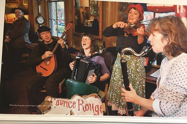 "Folk band singing and playing instruments in rustic room with ""Caprice Rouge"" sign"