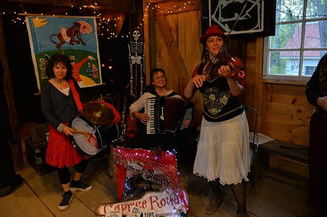 Three musicians with instruments playing in a rustic room with string lights and art in the background