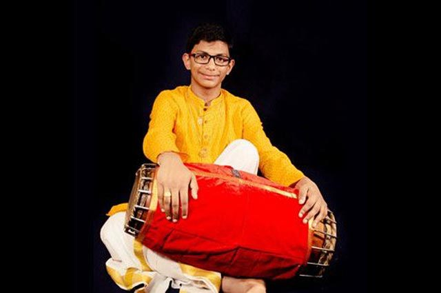 A teenage boy in a yellow outfit holding a red Indian percussion instrument, similar to a drum