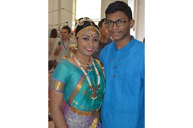 A woman and teenage boy in traditional Indian garb; her outfit is teal, gold, and purple with jewelry and his is royal blue