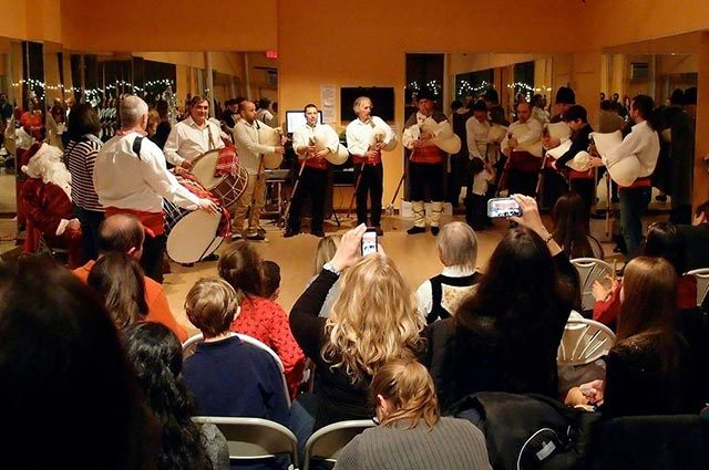 Drummers and bagpipers performing before a gathered audience