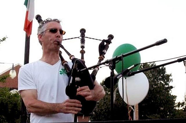 Bagpiper practicing outdoors with a flag and balloons behind him
