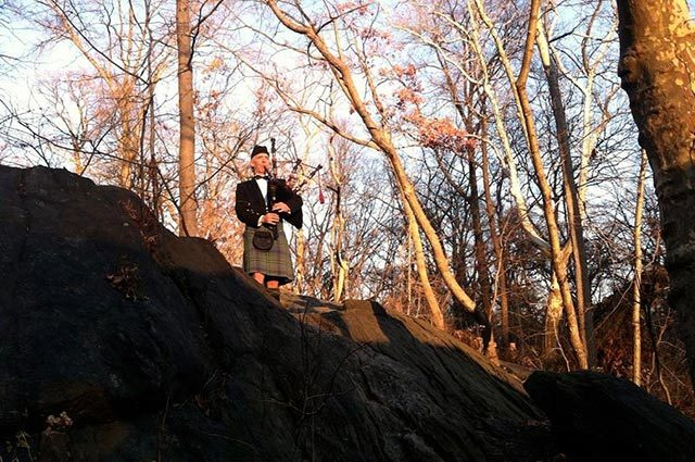 Bagpiper in kilt standing on a hillside in the woods playing the instrument