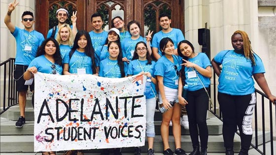 "A group of students standing on a staircase outside of a building, holding a sign which reads ""Adelante Student Voices"""