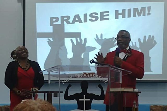 "Minister teaching from a stage standing in front of ""Praise Him"" image"