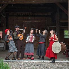 Five folk band members playing an assortment of instruments in front of a barn