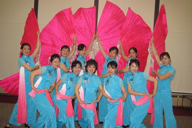 Chinese dance group wearing matching aqua sarongs and pink ribbons standing in front of large pink fans