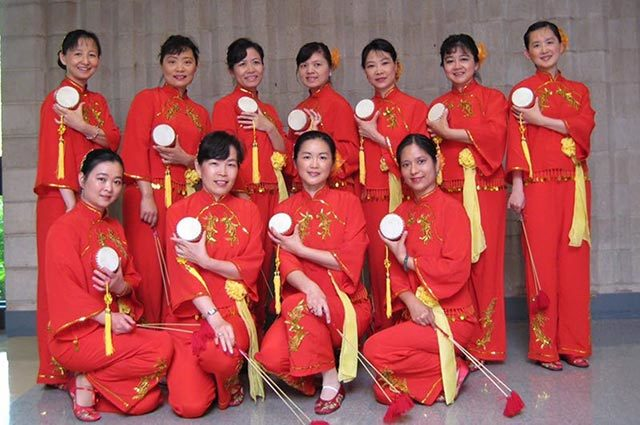 Eleven dancers wearing red holding white objects used in their dancing
