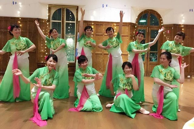 Ten dancers in a wood paneled room with matching green, pink, and white outfits