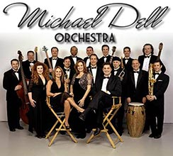"""Orchestra of 17 instrumentalists and vocalists in formal dress above them says """"Michael Dell Orchestra"""" in black letters, links to performer's website"""