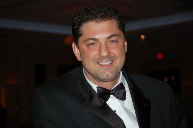 Photo head shot of singer wearing a black tuxedo