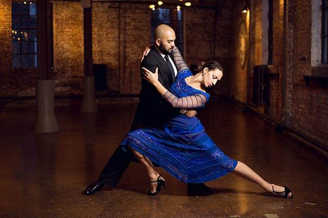 Tango dip performed by man in suit and womain fancy blue dress in a large, dark ballroom