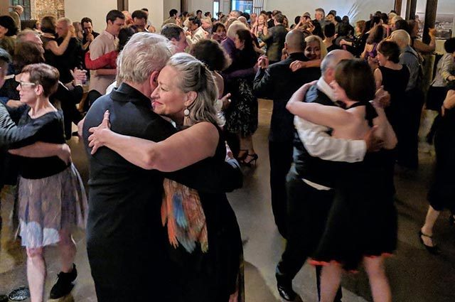Room full of many couples embraced and dancing