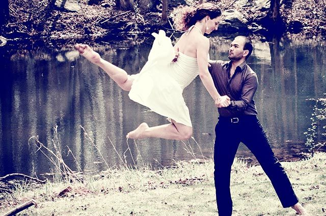 Male dancer supporting female partner's athletic dance leap outside near a stream