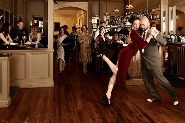 Elegant couple dancing in a cocktail bar as patrons in 1920s dress look on