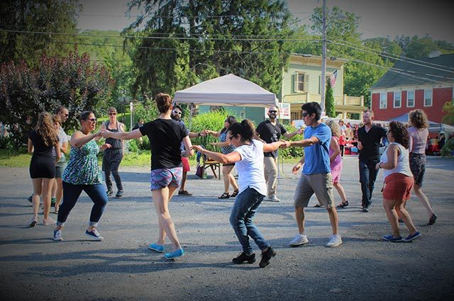 People dancing in a circle outdoors