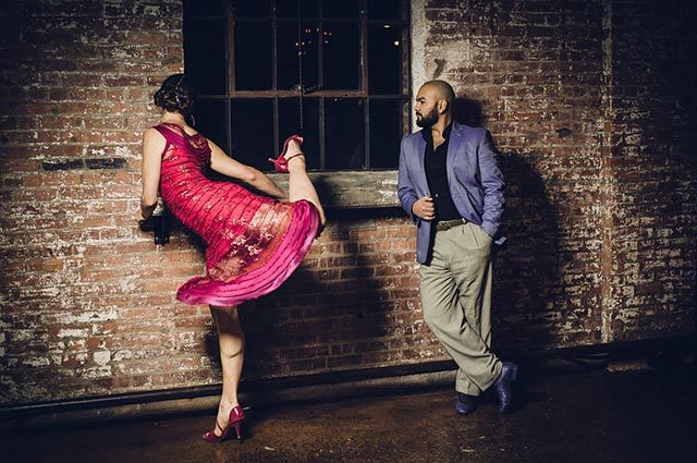 Man watches dancer practice her moves in front of window, as he leans on a brick wall
