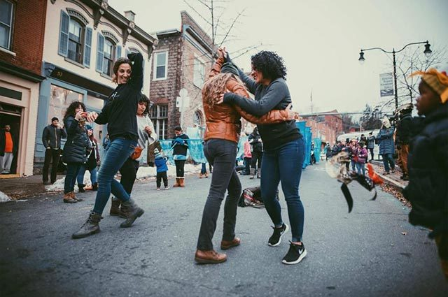 People dancing in the street at an outdoor festival
