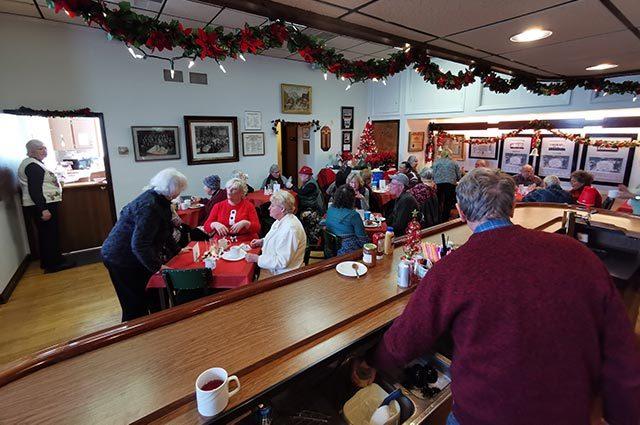 Angle behind a bar of people enjoying food and seasonal decorations