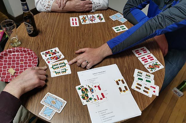 Three players enjoying traditional German card game