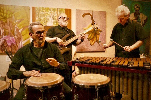 Latino musicians playing guitar, bongo drums and xylophone
