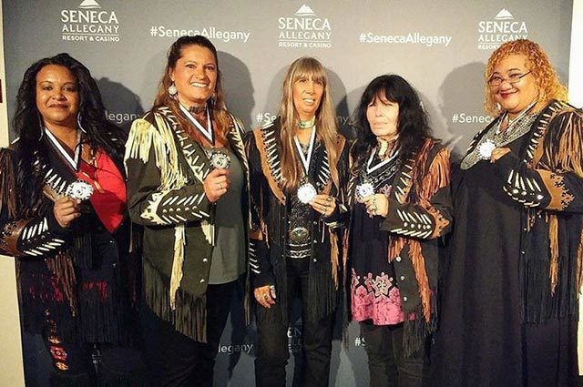 Performers in Native-style fringe jackets, holding metals around their necks, standing in front of a backdrop with logos