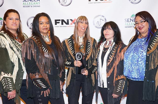 Full group in Native-style fringe jackets standing in front of a backdrop with logos
