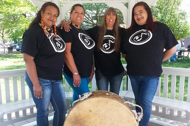 Group of four in black t-shirts and jeans stand around a large drum in a gazebo