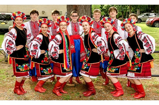 Twelve teenage dancers in traditional dress standing outside