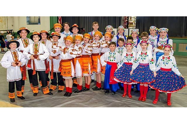 Children's dance group in colorful traditional dress standing outside