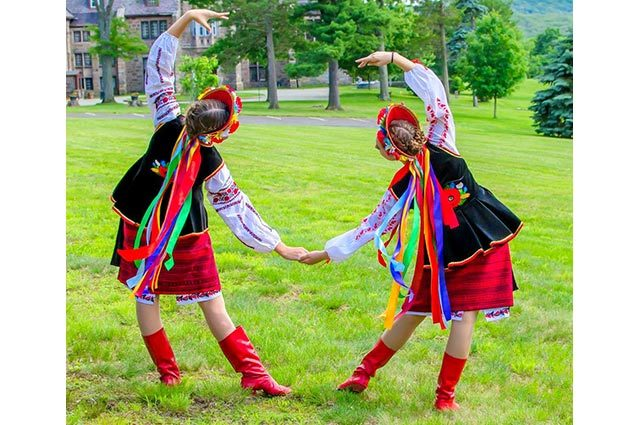 Two dancers in folk dance pose wearing costumes with flowing colorful ribbons