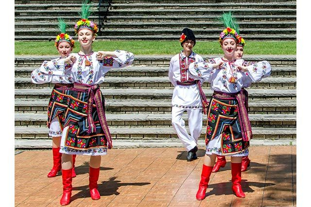 Five costumed dancers in a performance outdoors in front of many steps
