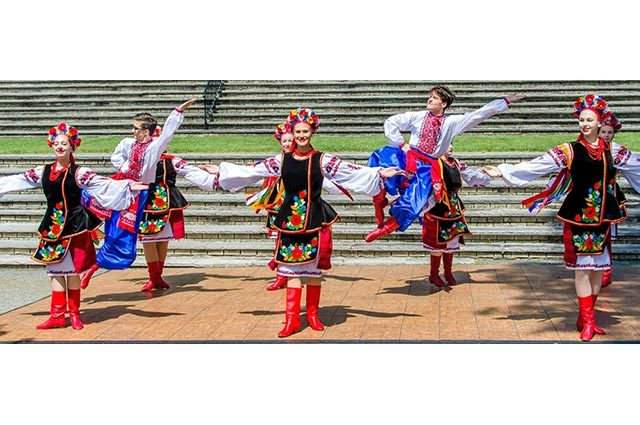 Dance group in costumes performing outdoors in front of many steps