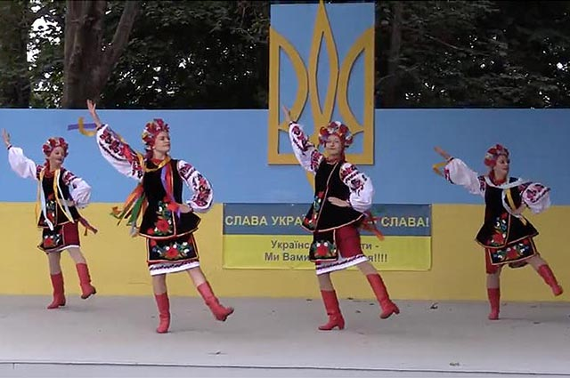 Four dancers in traditional red costumes and boots on a stage outside