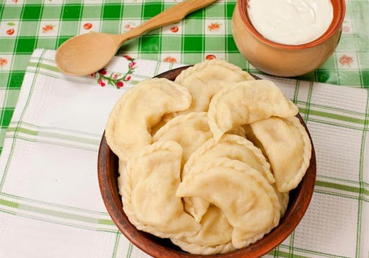A plate of traditional Ukranian dumplings on a tablecloth setting
