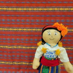 Handcrafted Mama worry doll against patterned background