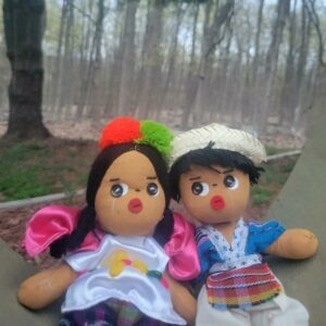 Two handcrafted worry dolls sitting next to each other outside in front of many trees.