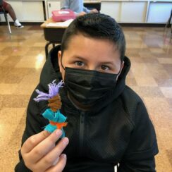 Young child wearing a mask holding their handmade worry doll in a classroom.