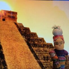 Two small handcrafted worry dolls imposed onto a background showing a Mayan temple.
