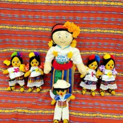 Handcrafted Mama worry doll on a patterned background with 5 smaller dolls aside and in front of her.